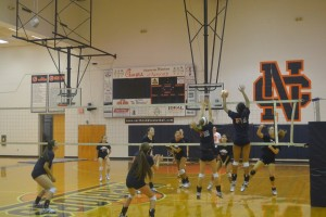 Senior Savannah Gonzalez swings; senior Simone Maxwell and junior Elizabeth Daniel blocks.