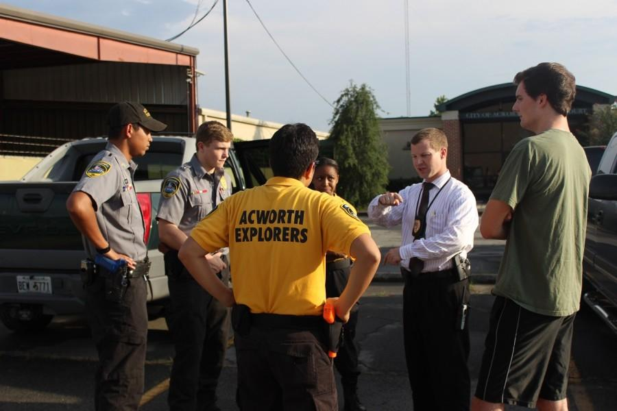 "The Explorers listen intently to their instructor, Sergeant Samson, as he explains the actions needed next. In the last scenario they failed to interview the suspects. ""The debriefing is helpful in learning what we did wrong, and will help us in for the competition"", says Explorer Canady."