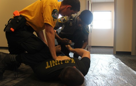 Adviser Jason Laroque is pinned to the ground in this overdose scenario. The acting officers are Wagner, who pins Laroque with his knee,  and Bernard who puts the handcuffs on because Laroque simulated becoming aggressive and starting to run away.