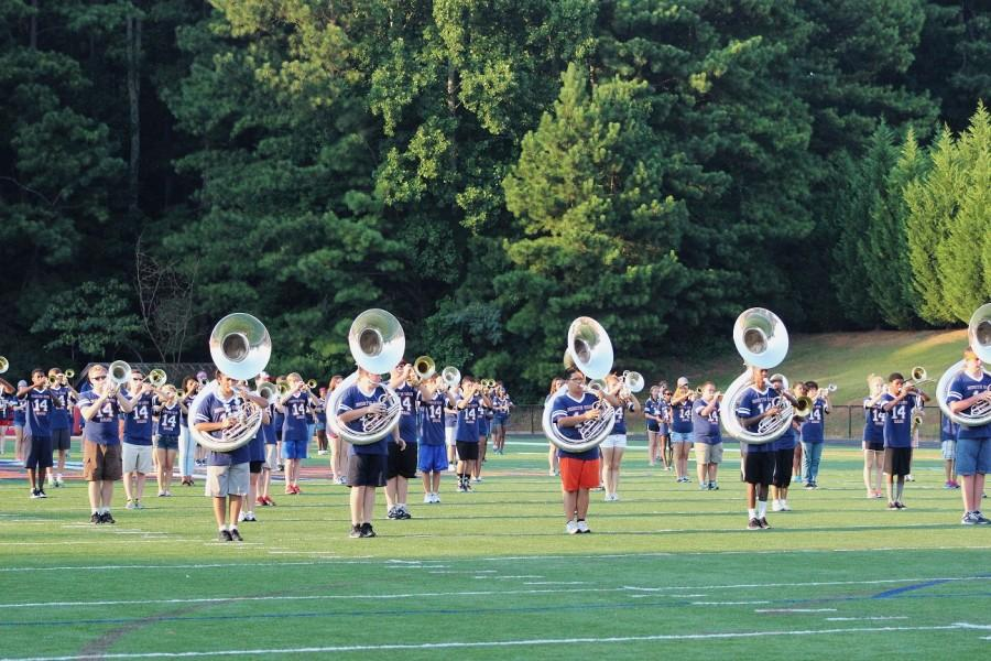 """The North Cobb High School Marching Band arcs it up to play the first three songs of their new show, """"Journey of a Champion"""". Last year the marching band took on the show of Les Miserables. """"This years theme is fun and I think the crowd will get more into it"""", senior drum major, Madison Luense, said."""