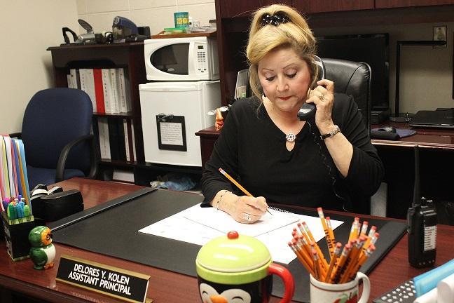 Mrs. Kolen, an expert multitasker, handles locker registrations and takes calls from parents.