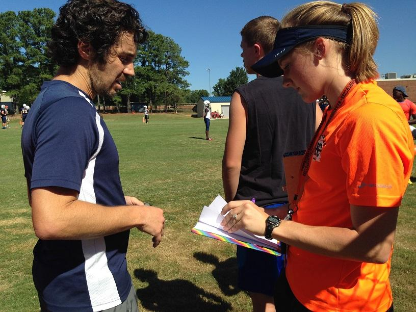 Former+NC+alumna+Sarah+Massey+and+now+head+cross+country+coach+discusses+runners%27+performance+with+Coach+Huff.+