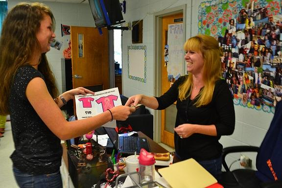 Mrs. Rankenburg supports striking out cancer by purchasing a Pink Out shirt from junior Riley O'Neill.