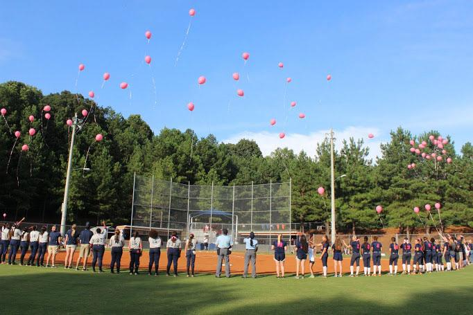 The++Lady+Warrior+softball+team%2C+the+umpires%2C+and+Marietta+Blue+Devils+look+up+at+the+pink+balloons+just+released+in+honor+of+survivors+and+fighters+of+cancer.%0A