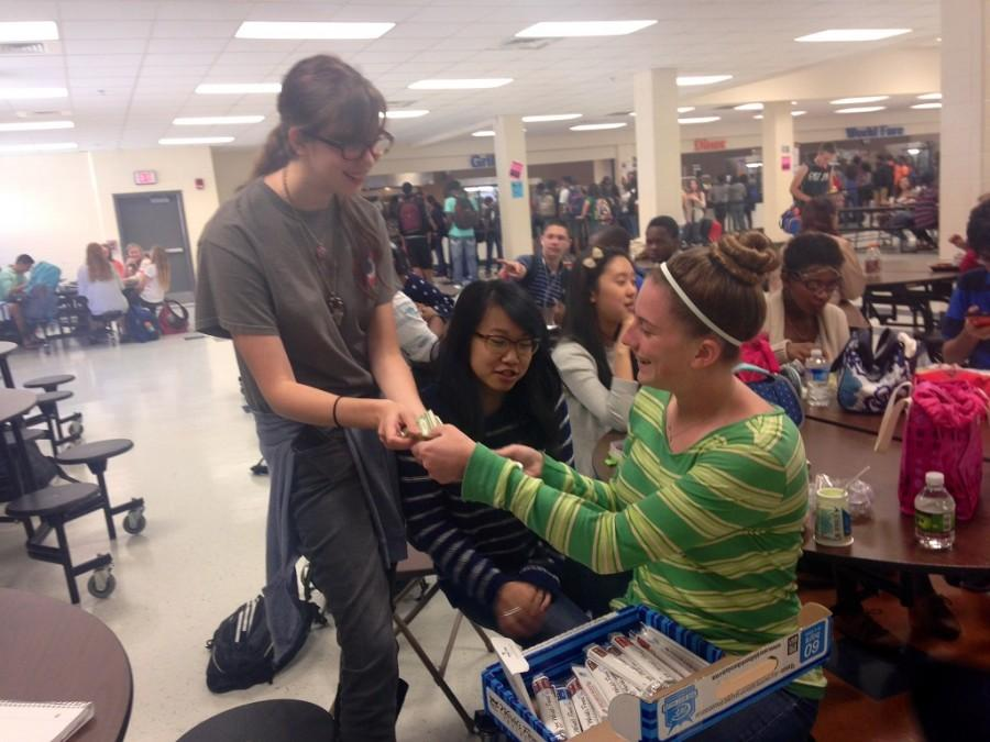 Junior Emory Perry sells orchestra chocolate to junior Hope Desimone during D lunch.