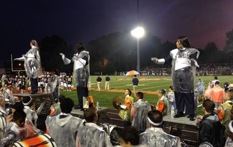 Drum majors Madison Luense, Sajal Patel, and Mia Jordan get ready for the signal to conduct the marching band to play the North Cobb's fight song.
