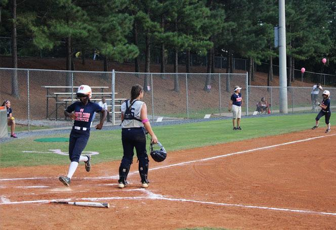 Sophomore Iman Muhammad runs to home base as senior Casey Page is running right behind her for another home run.