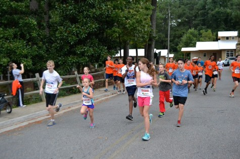 Warriors run with local kids to help them finish their 1K. North Cobb students dressed in orange as beacons for the kids.