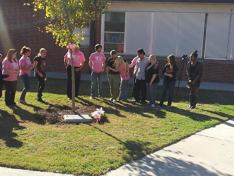 Chorus students gather around the newly planted tree to honor Dr. Foster.