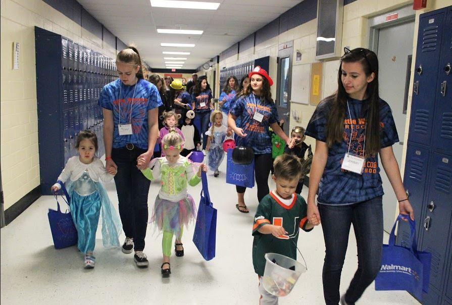 Students in the Early Childhood class help walk their trick-or-treaters to each classroom to greet students and grab goodies along the way.
