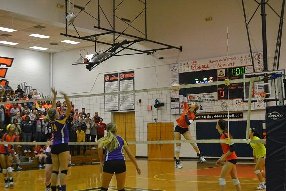 Savannah Gonzales, number four, spikes the ball over the net, hoping for a point against East Coweta. She finished the game with 22 kills, the highest of the team.