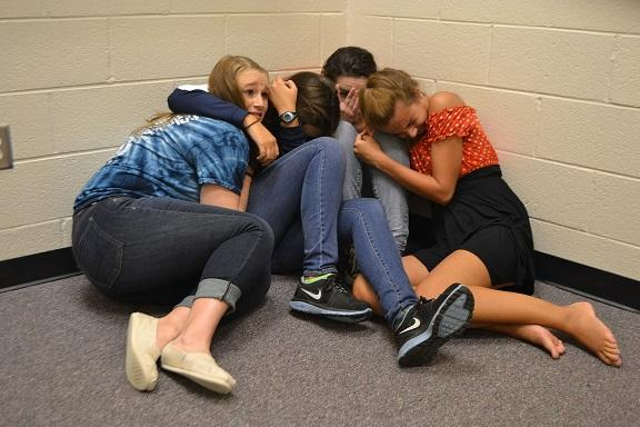 """Students huddle together for safety after a 'code red' alert was issued. With the doors locked and lights off, teachers strive to keep students calm and safe until further notice. """"It was definitely scary and having to stay in a tiny room with 30 students didn't make it any better,"""" senior Sarah Reagan commented.  Students' fears were alleviated when Dr. Page came on the announcements to alert any new developments. his calming voice kept the school from panic."""
