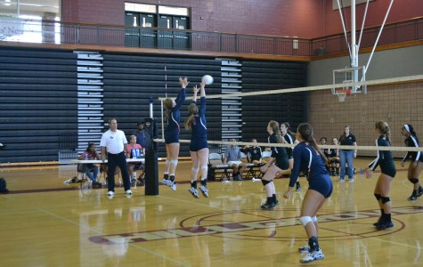 Senior Savanna Gonzales (4), outside hitter, and sophomore Jenna Woodruff (20), middle hitter, block opponent's swing.