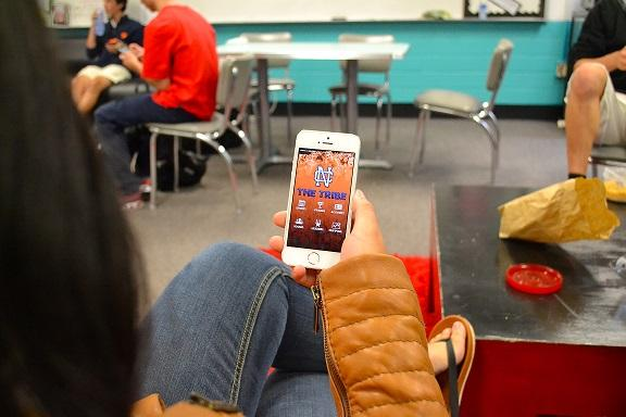 """Junior Kiky Etika checks the Tribe App during lunch. """"I always check on Mondays because I want to know how to plan my week,"""" she said. """"I think the Tribe App is really cool. It's a good addition to the school."""""""