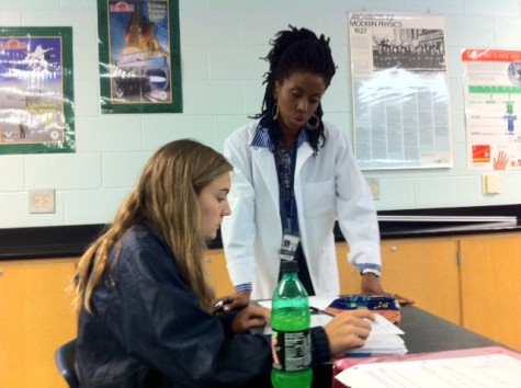 Senior MaryEllen Hawkland receives instruction from Ms. Walker during her Physics class. Ms. Walker structures her groups based on gender, believing that throwing a girl in the mix of a group of males can make it hard for the female student to get her point across.