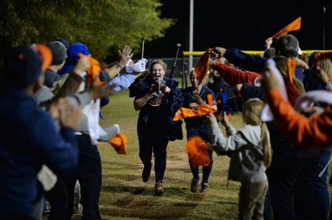 Seniors Bryanna Vazquez and Carli Troutman run through the lines of supporters after their last high school softball game.