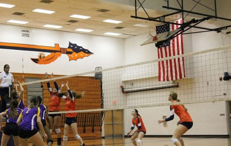 Juniors Taylor Parrish (10), setter, and Lizzy Daniel (7) , middle, attempt to block a hit from the opposing team.