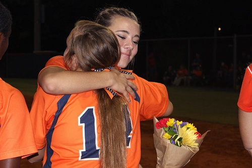 Senior Casey Page hugs her team member junior Taylor Krause lovingly with the flower bouquet that was provided by her team mates.