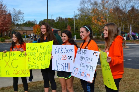 Seniors Maria Mesa, Jessica Luna, and Sarah Reagan, junior Riley O'Neill, and sophomore Mackenzie Union display homemade posters. The North Cobb Girls Varsity team spent the whole race cheering on the boys.