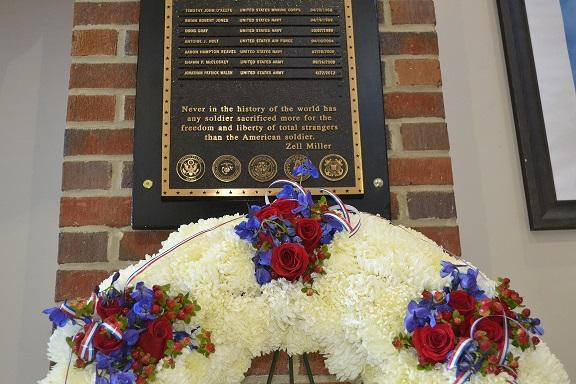 In the North Cobb lobby, a commemorative wreath stands under the list of deceased alumni. Before the program, the names were read out loud and a bell rung in remembrance.
