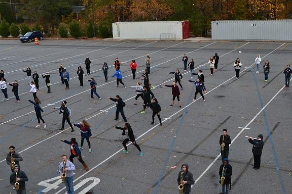 Colorguard members dance without the seniors on the bus port during act two of the show.