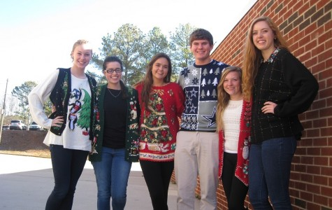 "Seniors Caleb Bacak, Savanna Gonzales, Melissa Kelsey, Victoria Wright, Lucy Clay, and Catherine Lamb gather around wearing their christmas sweaters for Tacky Sweater Day. Gonzales said cheerfully, ""Tis the season to be tacky."""