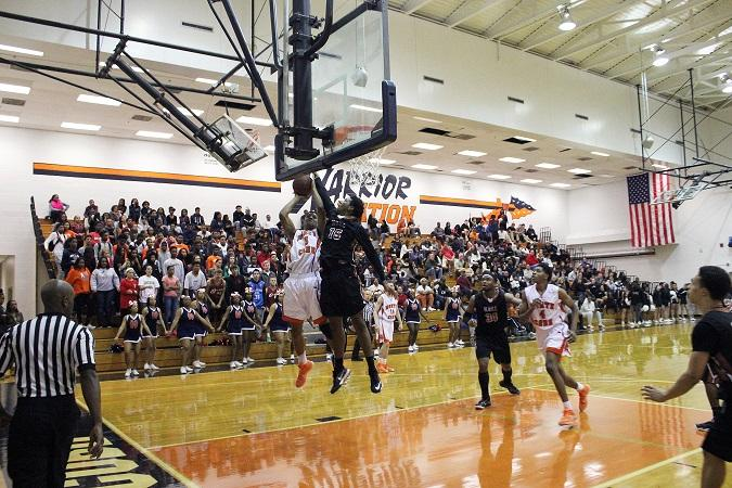 Isaiah Clemmons, senior forward, attempts a slam dunk eventually blocked by opponent, number 15.