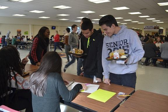 """After grabbing their lunch, seniors Danny Maldonado and Christian Duque check their senior quotes. Duque said, """"It was hard to pick one. I changed mine at least three times."""" Maldonado added on saying how checking it reminds him that senior year is almost over. In the background seniors Nia McGaugh and Iman Clark laugh about their senior quotes. Clark was happy with her quote and said, """"Senior quotes are a good way to have people remember you."""" McGaugh builded on Clark's idea: """"They can remember things like your humor or your positivity."""""""