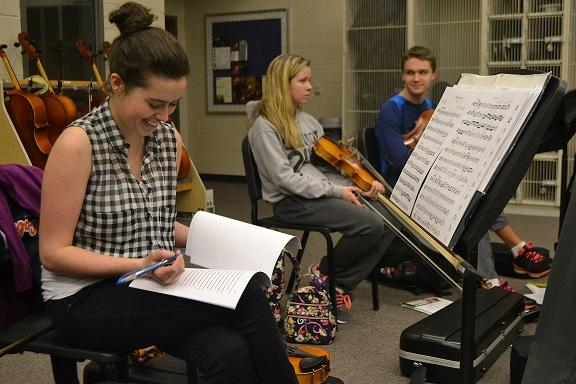 Victoria Wright focuses on learning and playing her viola music. While the conductor focuses on a different section, Victoria happily reads over and edits a classmate's AP Lang paper.
