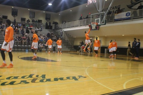 Before the game begins the players practice shooting hoops. Junior Ricky Shearman practices a lay up.