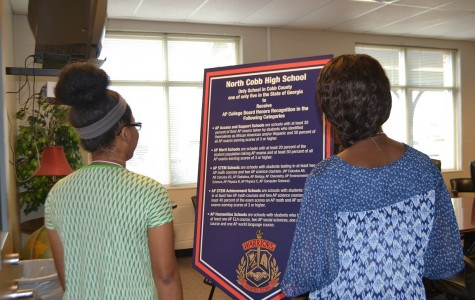 """Juniors Laurie Francois and Mercedes Gray observe the poster board proclaiming NC's latest achievement. The display stood proudly at the Magnet Open House. """"I'm proud of North Cobb because we worked really hard to get where we are and the students deserve to be recognized,"""" said Gray."""