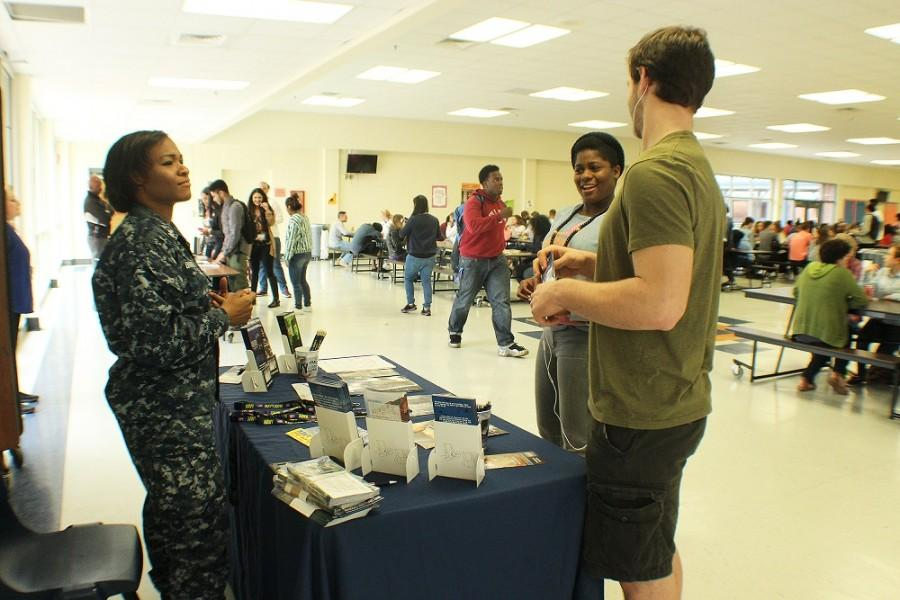 "Petty Officer Kelly Brantley talks to juniors Kayla Augustine and Josh Wright about their possible future in the United States Navy. Tarleshia Jean Pierre: ""Why did you decide to be a recruiter?"" Brantley: ""The navy did a lot for me, the education, [the financial help]... [it has] various benefits―I wanted to share that with others."""