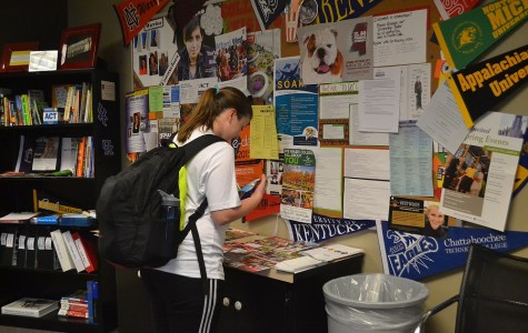 """On her way back to class, junior Riley Swab stops by the Future Shop to take a look over the numerous college pamphlets and folders that NC placed there. """"There's a lot of colleges that I've gotten information about that I probably wouldn't have looked up,"""" she said. """"It's just easier to drop by and get information so I think it's cool North Cobb has this."""" NC will be hosting a college visit from Shorter University tomorrow, March 10."""
