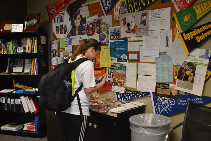"On her way back to class, junior Riley Swab stops by the Future Shop to take a look over the numerous college pamphlets and folders that NC placed there. ""There's a lot of colleges that I've gotten information about that I probably wouldn't have looked up,"" she said. ""It's just easier to drop by and get information so I think it's cool North Cobb has this."" NC will be hosting a college visit from Shorter University tomorrow, March 10."