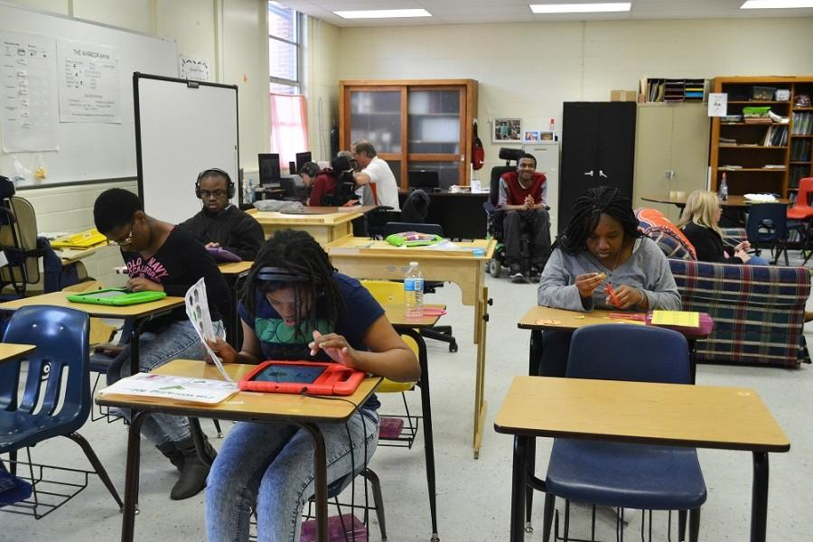 Mr. Smith's special education students enjoy leisure time with various activities. Some work on their introductory work while others listened to music.