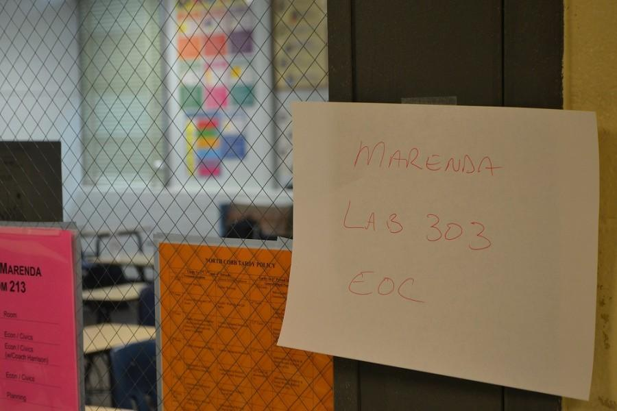 Economics teacher Mr. Marenda taped a sign to his door to indicate to his students where they will be taking the first part of their mid-semester EOC.
