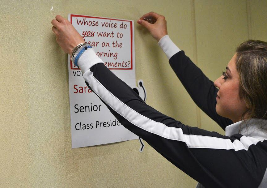 Junior Sarah Sutley hangs one of her many posters to campaign for senior class president. With class elections fast approaching, posters like Sutley's start to pop up all around school.