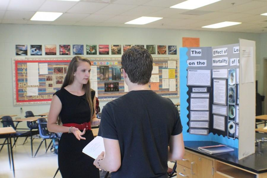 Junior+Maddie+Arnold+explains+her+project+to+Haven+Hardgrave+during+the+Posters+Symposium+for+ASR.