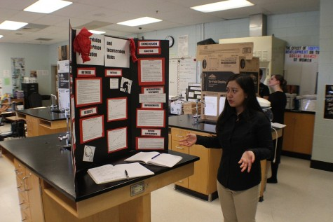 Kiky Etika shows off the data on her poster board to fellow junior Nathaniel Bigelow during the Posters Symposium.