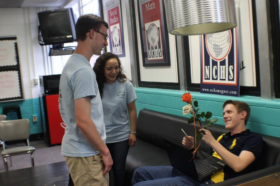 Seniors Sean Brennan and Jacky Banos present junior Holden Haley with a rose for National Honors Society inductions. Haley said of his induction introduction,