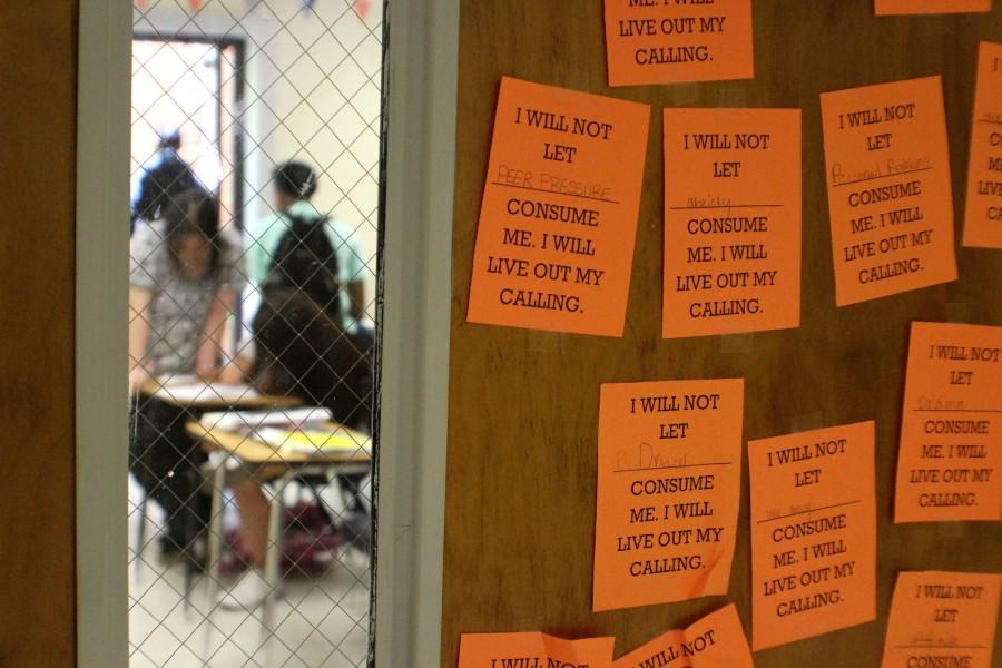 Mrs. Lipham's door catches the eye of viewers with bright orange placards for a unit activity that corresponds with Ayn Rand's Anthem, inspired by Ms. Gerlach's idea to have students better understand dystopic issues.