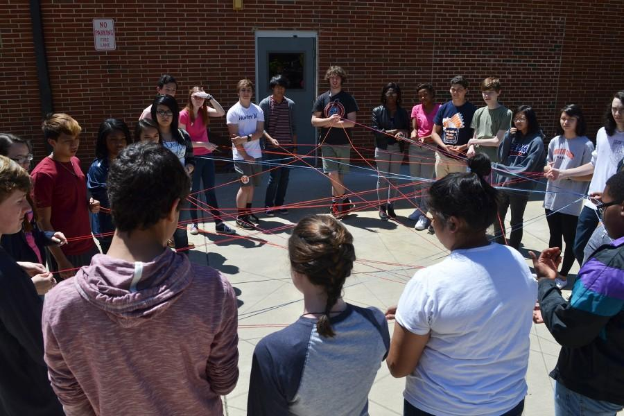 "Enjoying the sunny weather, AP World History teacher Ms. Galloway takes her class outside to provide a more clear understanding of the relationships between the countries during World War I. Sophomore Diana Casco, leading the group by pulling the yarn as the country Serbia, commented, ""This exercise gives me a visual understanding of WWIーit's really helpful."""
