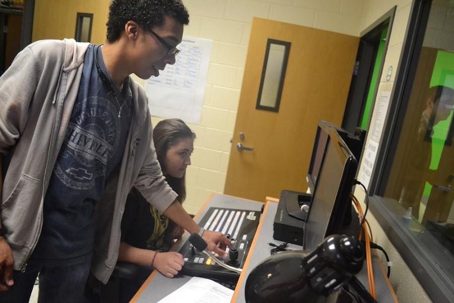 Senior Producer DJ DeBois helps junior Marissa Rodriguez edit a video.