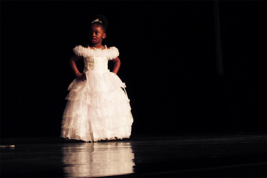 Lillie Fuller, the first contestant of the Junior Little Miss Warrior Pageant, walks across the stage for the first time in the competition without the help of her mother, sporting her beautiful evening wear.