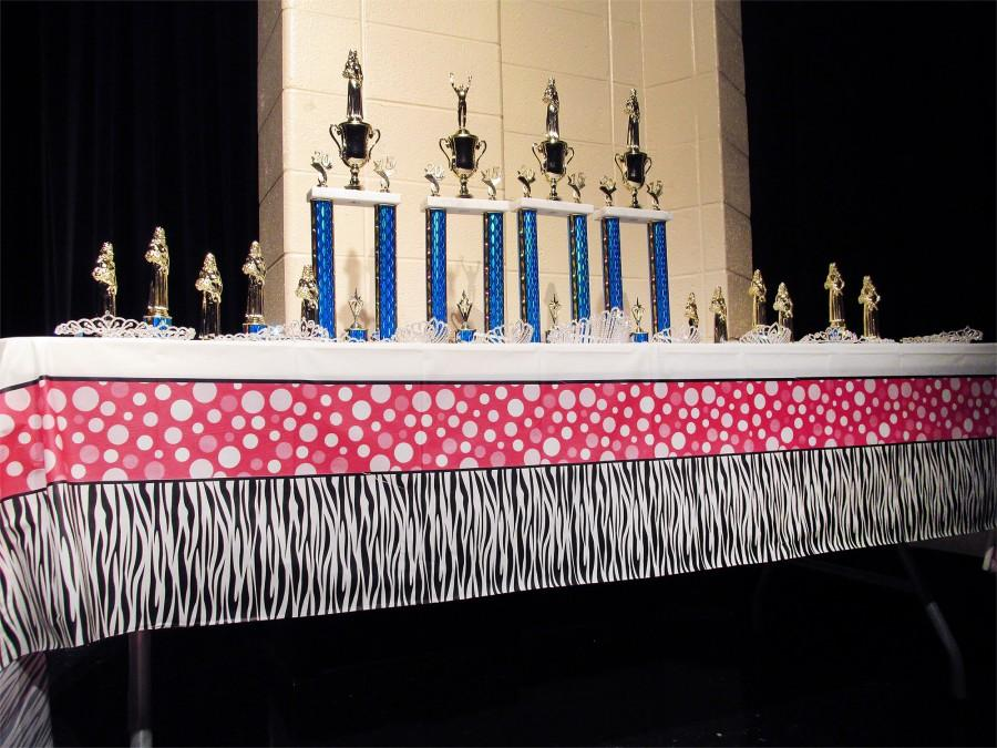 The trophies and tiaras were displayed on a table on stage throughout the competition, inspiring contenders to work even harder for the judges.