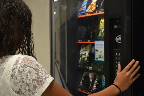 Freshman Tylan Eley struggles to decide between trail mix and popcorn. With the new restrictions on school vending machines, students choice of snacks are extremely limited. Tylan complained about the limited options.