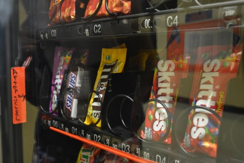 """Senior Nimzy Kabibi jams her finger into the button for the third time struggling to get her bag of Skittles. When reporter Chloe Roberson asks her about the change she states, """"terribly inconvenient."""""""
