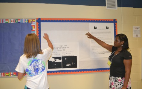Magnet seniors Mackenzie Union and Dominique Cooper pitch in to reconstruct the Magnet Bulletin Board, a place where SAT information and events will be posted.