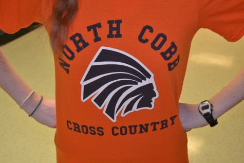 A student shows their school loyalty by wearing their Cross Country team shirt in the NC's signature orange color.