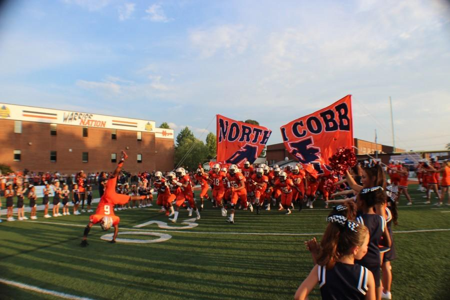 NC's varsity football team running through the banner before kickoff.